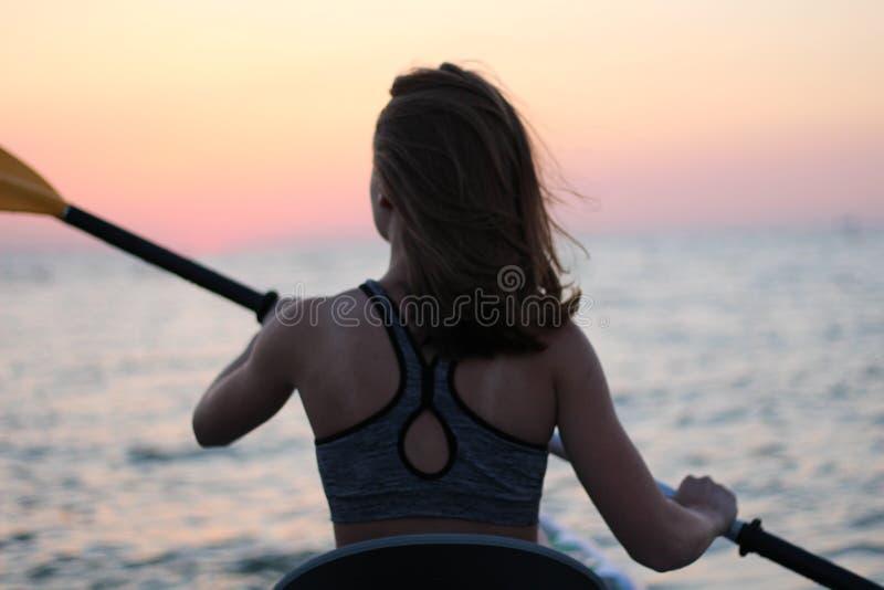 Kayak fahrende Frau im Kajak Mädchen-Rudersport im Wasser von einem ruhigen See lizenzfreie stockfotografie