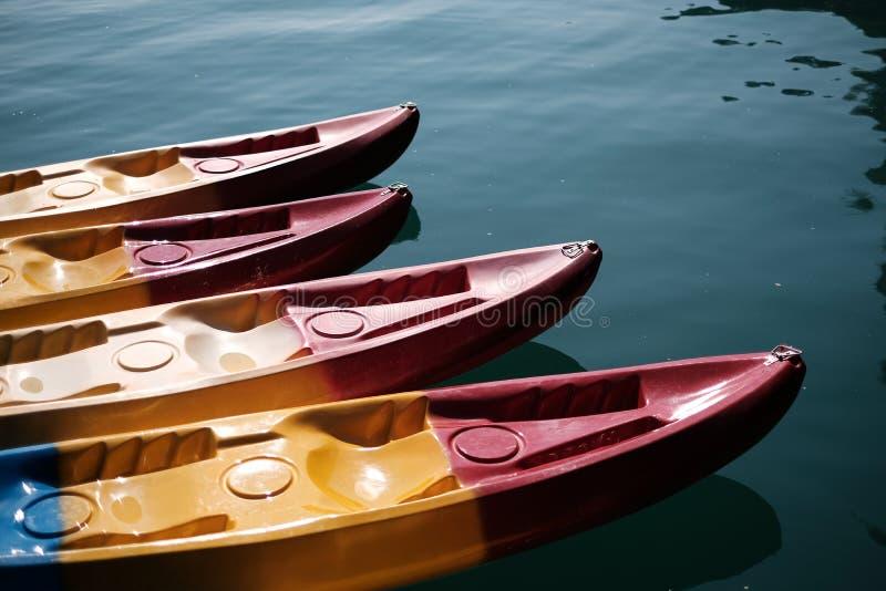 Kayak fahrendes Sitzen auf dem Ufer eines See Konzept-Fotos Sport-bunter Plastikkajak mit Wasser im Hintergrund lizenzfreies stockbild