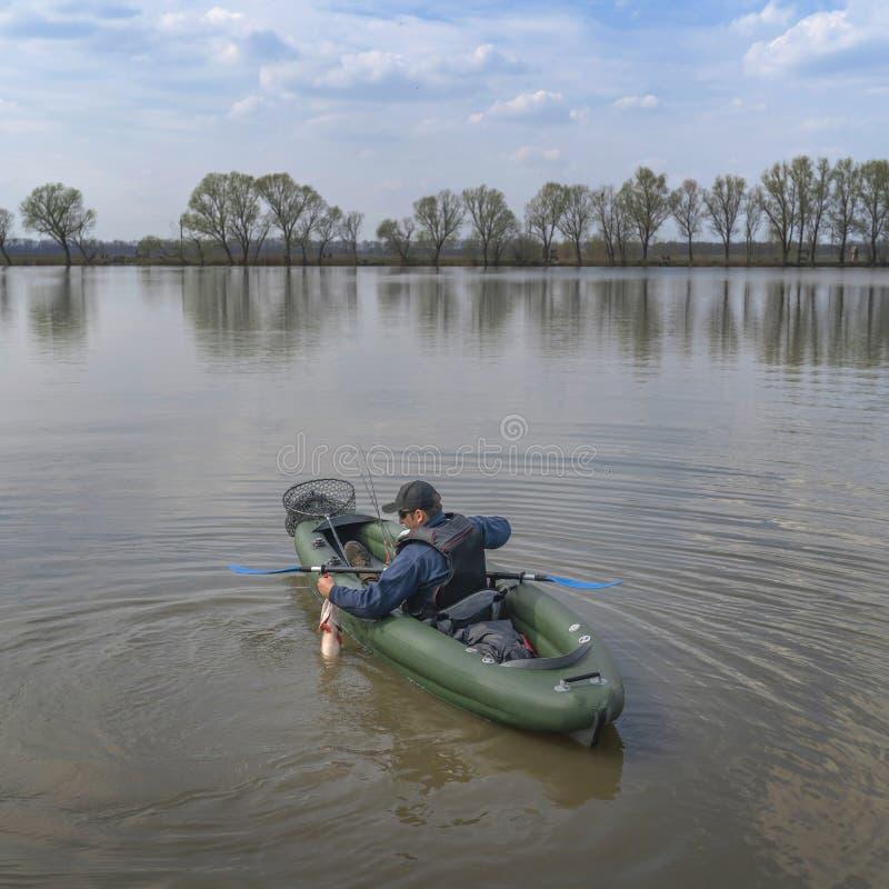 Kayak fishing. Fisherman caught pike fish on inflatable boat with fishing tackle at lake stock images