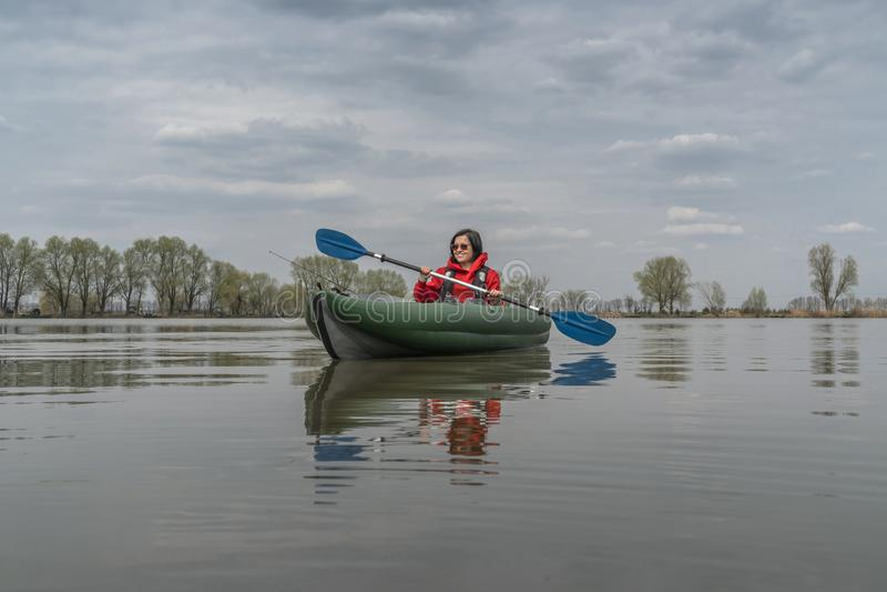 Kayak fishing at lake. Fisherwoman on inflatable boat with fishing tackle stock photo
