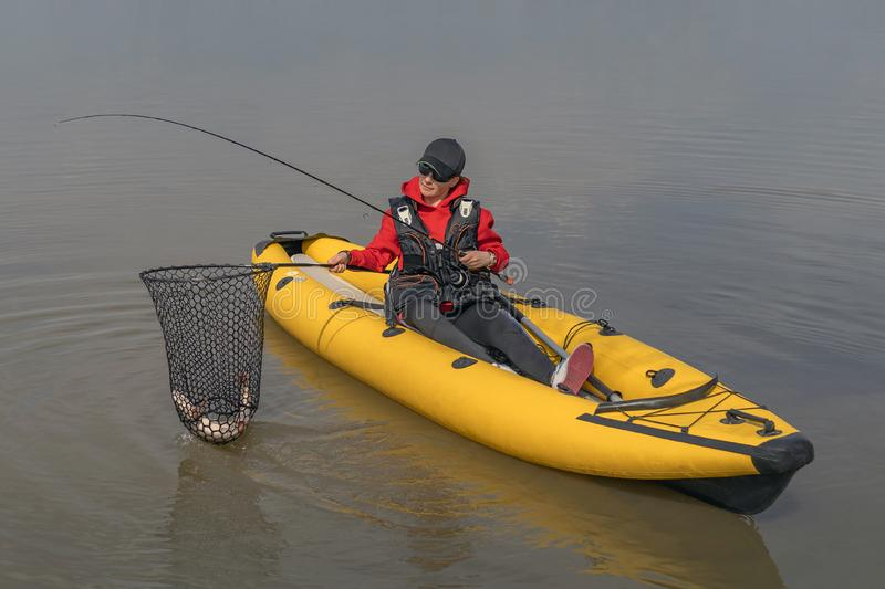 Kayak fishing at lake. Fisherwoman with pike fish on inflatable boat with fishing tackle royalty free stock images