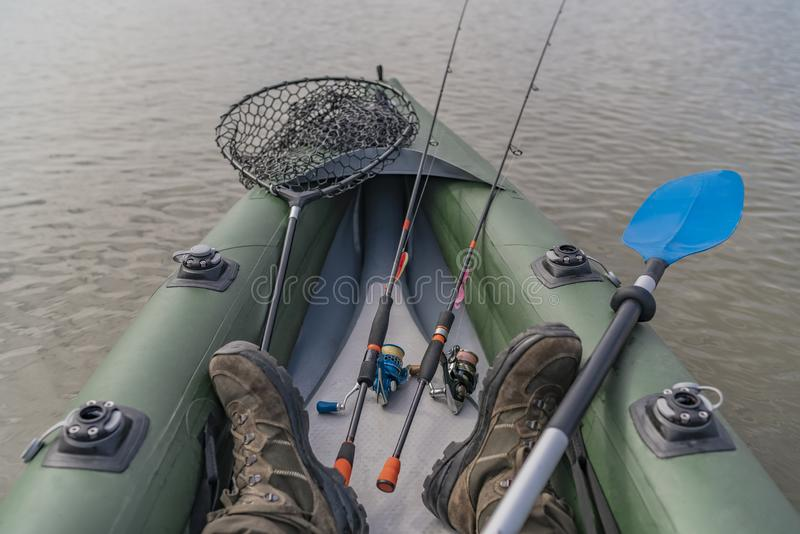 Kayak fishing at lake. Legs of fisherman on inflatable boat with fishing tackle.  stock photography