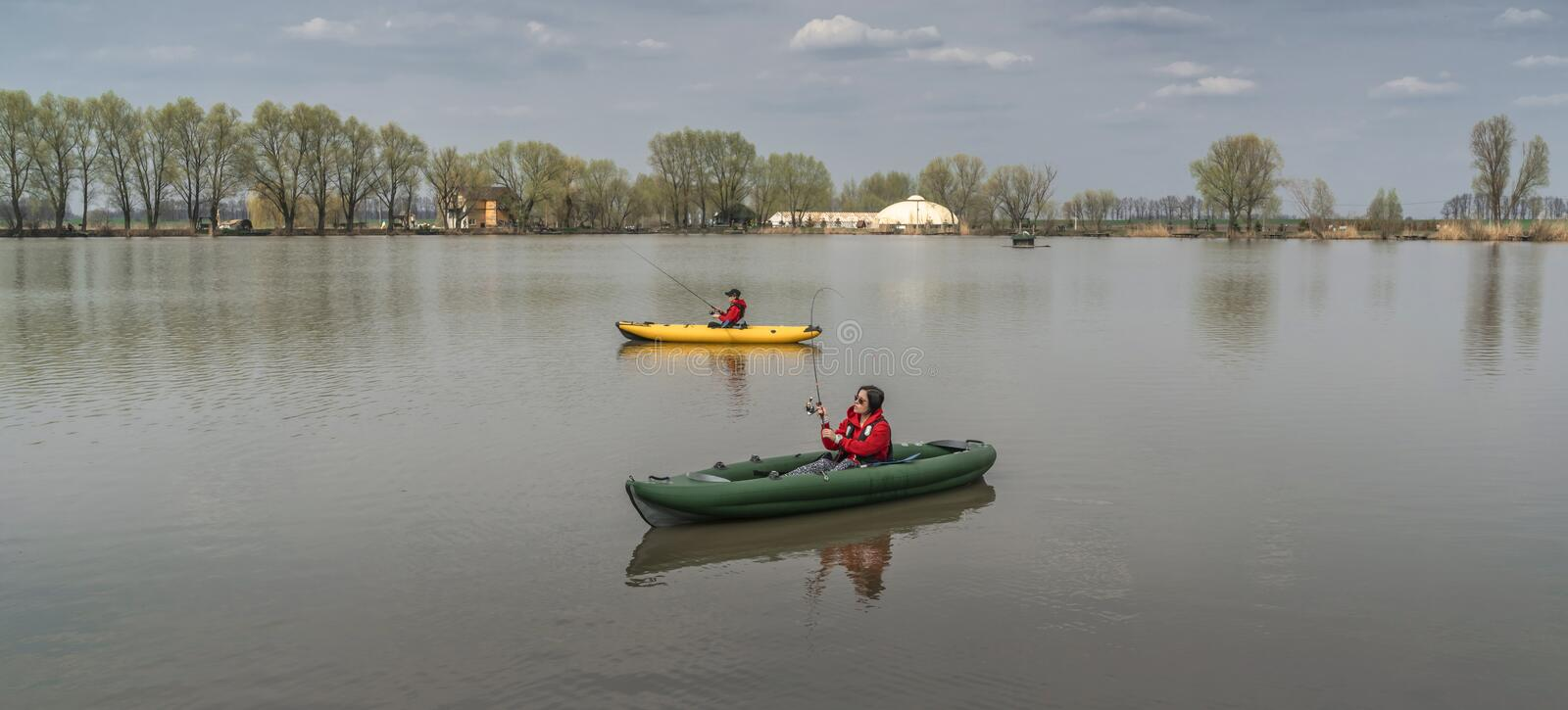 Kayak fishing at lake. Two fisherwomen on inflatable boats with fishing tackle stock images