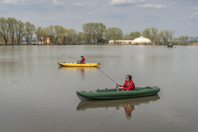 Kayak fishing at lake. Two fisherwomen on inflatable boats with fishing tackle royalty free stock images