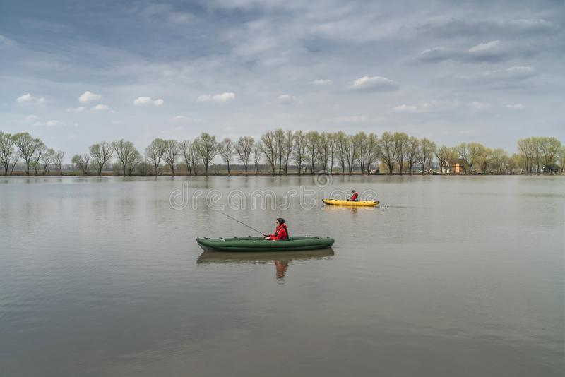 Kayak fishing at lake. Two fisherwomen on inflatable boats with fishing tackle royalty free stock photography