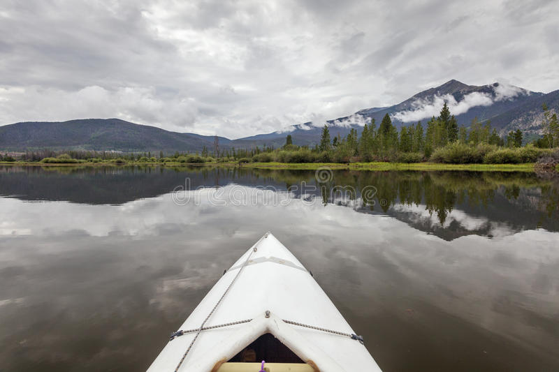 Kayak on Lake Dillon. Bow of a white kayak on Lake Dillon in Colorado Rocky Mountains, cloudy sky with water reflections stock photography
