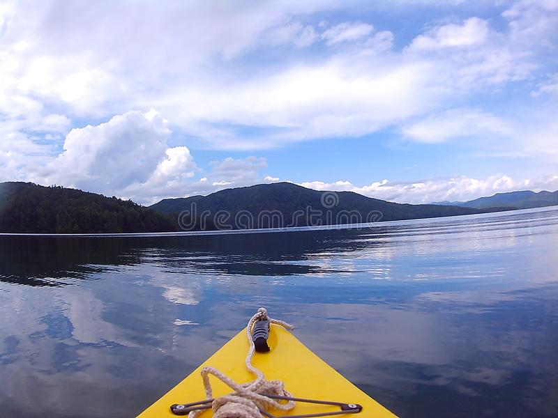 Kayak on lake. Yellow kayak on lake with mountains. Clouds with blue sky stock images