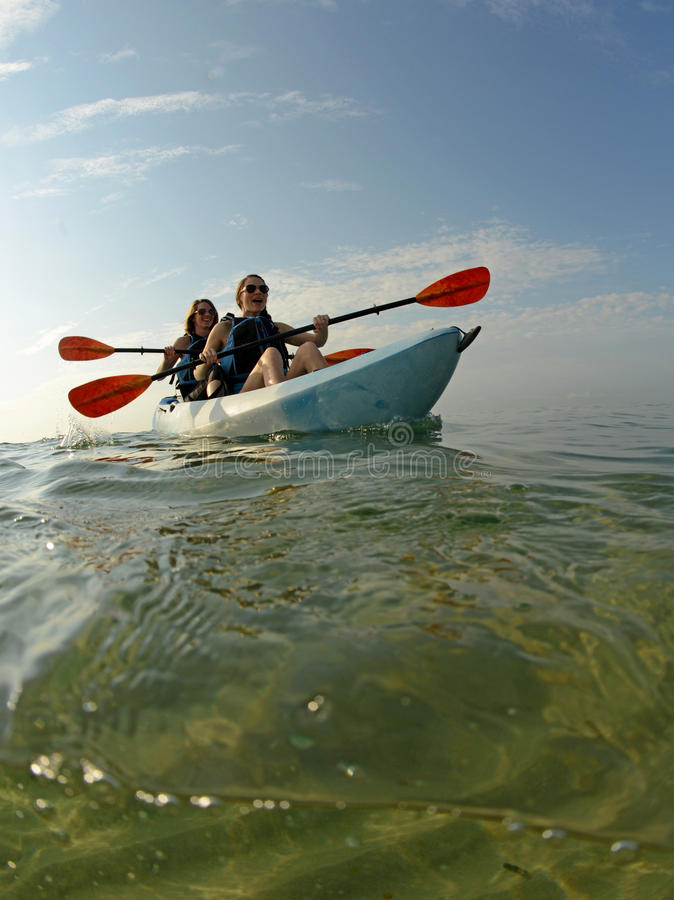 Kayak in ocean with two women royalty free stock photography