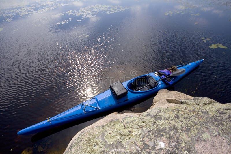 Kayak Beside A Rock. A blue touring kayak sits beside a rock on a lake stock photography