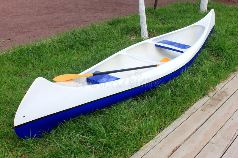 Kayak. Sitting on the grass near a wooden pontoon royalty free stock image