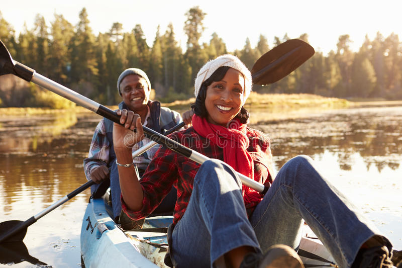 Kayak supérieur d'aviron de couples d'Afro-américain sur le lac photographie stock