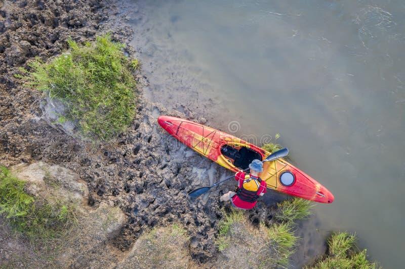 Kayaker σε μια λασπώδη ακτή του μελαγχολικού ποταμού στοκ φωτογραφίες