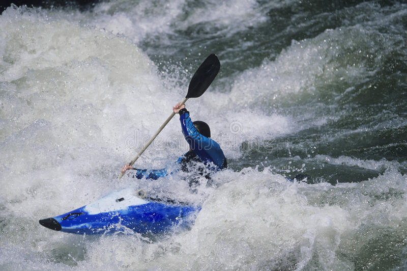 Kayaker che rema attraverso le rapide dell'acqua bianca immagine stock