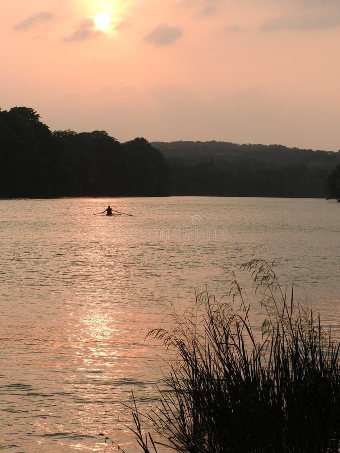 Kayaker en la puesta del sol imagenes de archivo