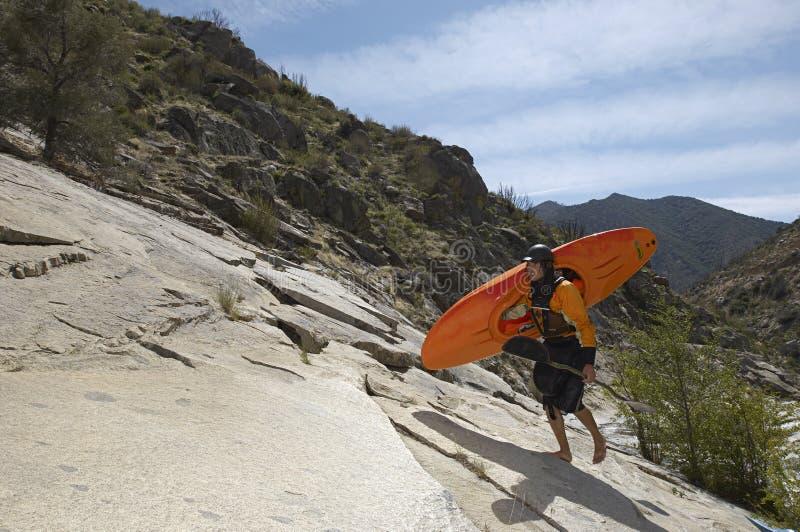 Kayaker femminile che cammina sulla roccia immagini stock libere da diritti