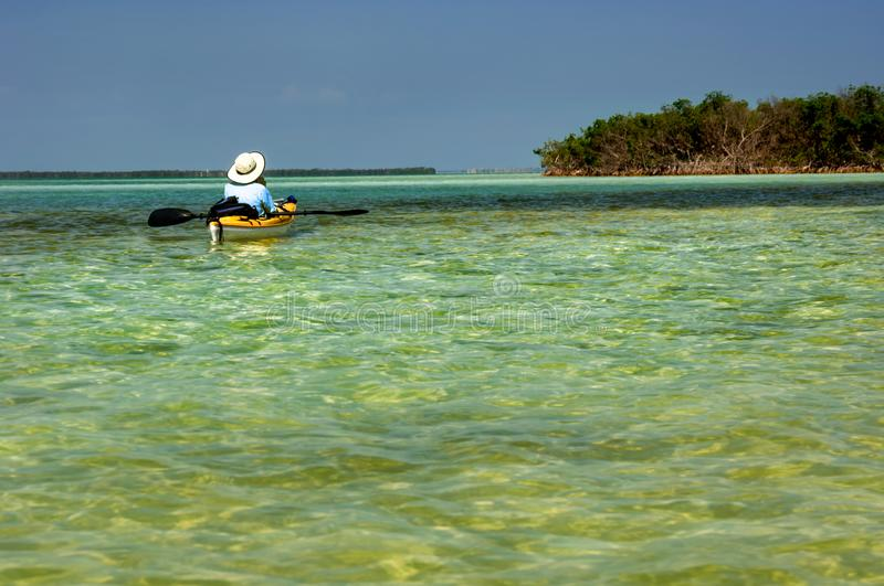 A kayaker floating in turquoise green waters in the Florida Keys. On a sunny blue sky day royalty free stock photography