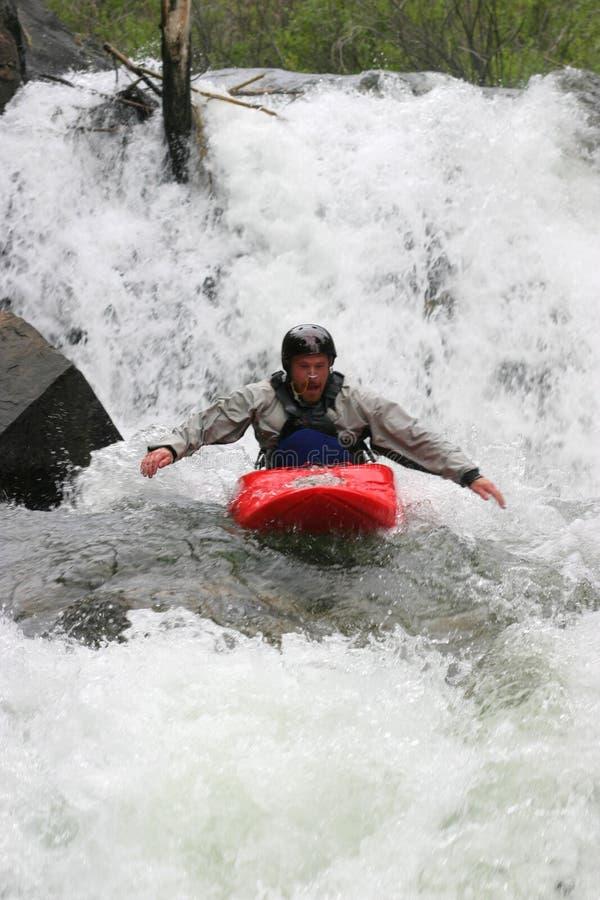 Kayaker hand paddling waterfall royalty free stock photo