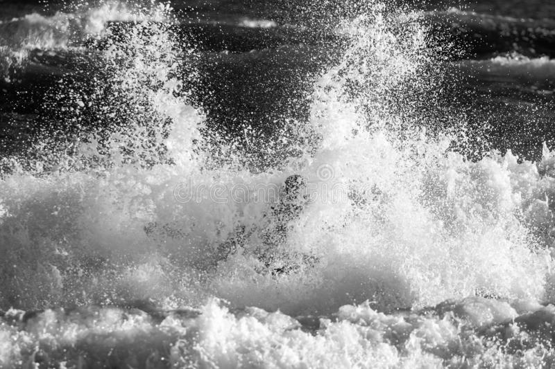 Kayaker and his boat under heavy surf stock photography