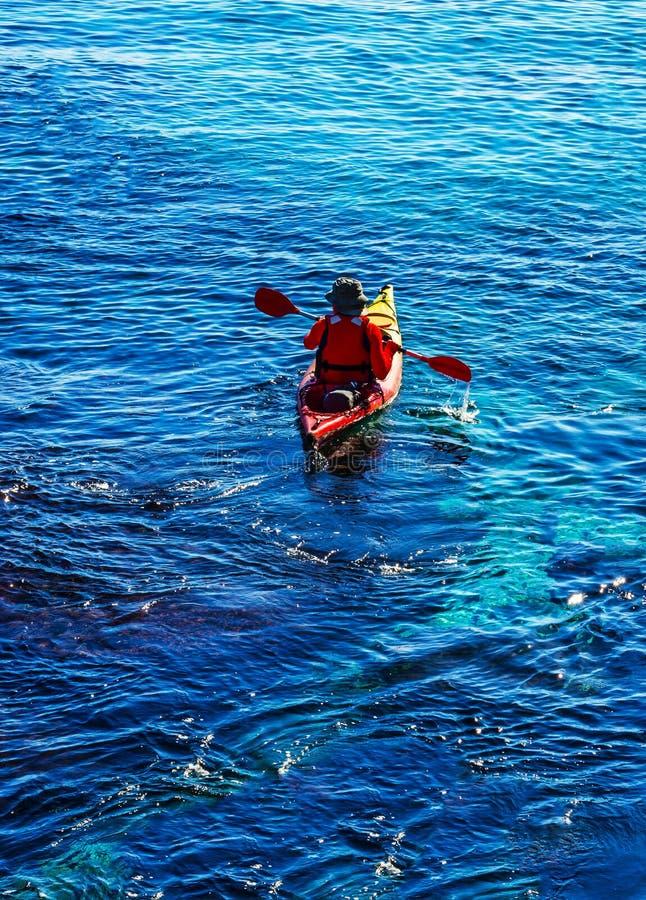 Kayaker mayor en un kajak por el mar, el deporte acuático activo y los leus fotografía de archivo