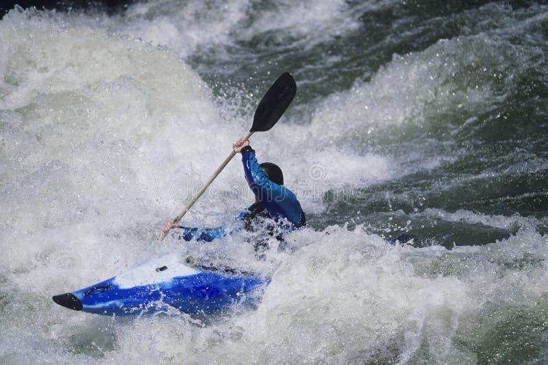 Kayaker Paddling Through White Water Rapids. Side view of a male kayaker paddling through white water rapids stock image