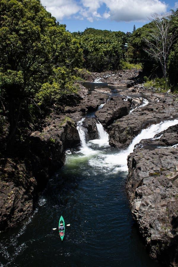 Kayaker que se bate contra la corriente en kajak verde en el río foto de archivo
