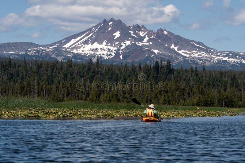 Kayaker que se bate en el lago hermoso de la montaña cerca de la curva, Oregon fotografía de archivo