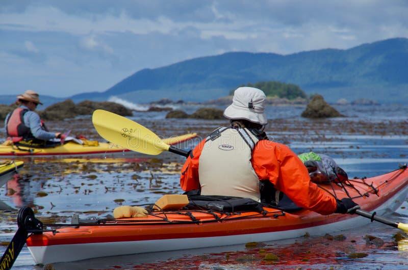 Kayakers в красочной шестерне отдыхают в заветренной стороне рифа около острова Checkaklis стоковые фотографии rf