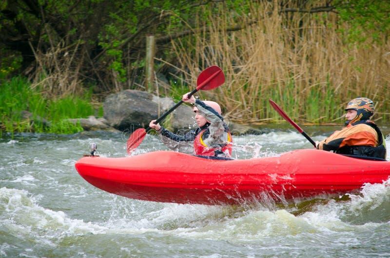 Kayakers ativos na água áspera foto de stock