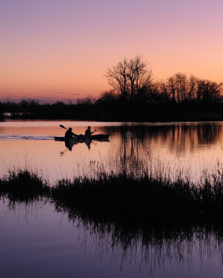 Kayakers en el amanecer foto de archivo libre de regalías