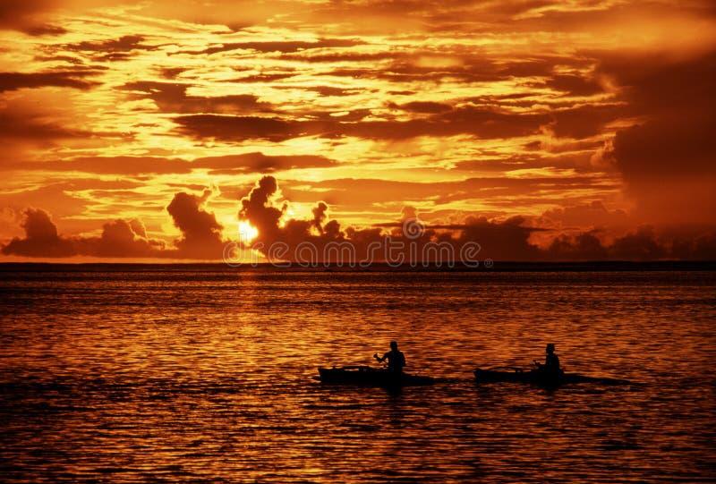 Kayakers en la puesta del sol imagenes de archivo