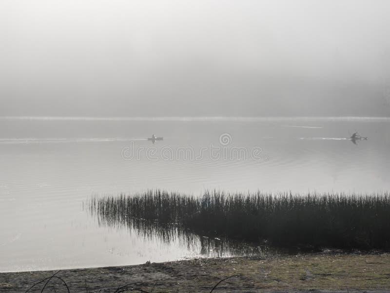Kayakers en un lago de niebla fotos de archivo
