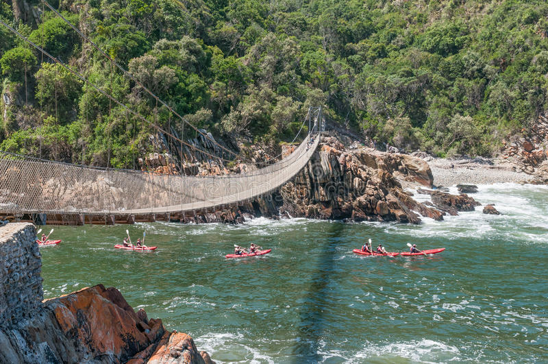Kayakers entering the Storms River gorge. STORMS RIVER MOUTH, SOUTH AFRICA - FEBRUARY 29, 2016: Unidentified kayakers passing underneath the suspension bridge to stock photo