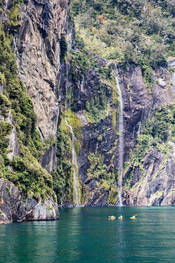Kayakers genießen die Landschaft und die Wasserfälle von Milford Sound, eins von Neuseeland-` s die meisten populären touristisch lizenzfreie stockbilder