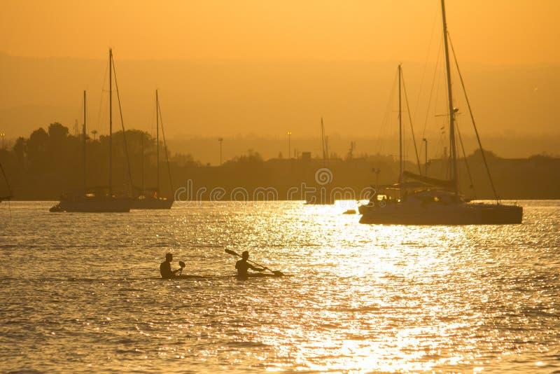 Kayakers no por do sol fotografia de stock