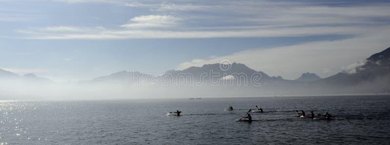 Kayakers på kajaken och kanoten som gör loppet på Annecy sjön royaltyfri fotografi