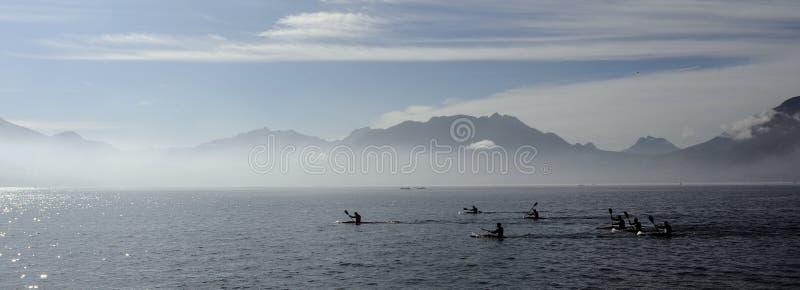 Kayakers på kajaken och kanoten som gör loppet på Annecy sjön arkivbilder