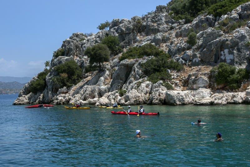 Kayakers paddlar n?rgr?nsande till den sjunkna staden av Simena av den Kekova ?n arkivfoton