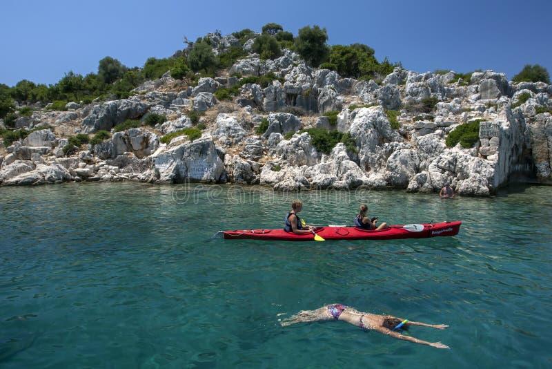 Kayakers paddlar n?rgr?nsande till den sjunkna staden av Simena av den Kekova ?n arkivbilder
