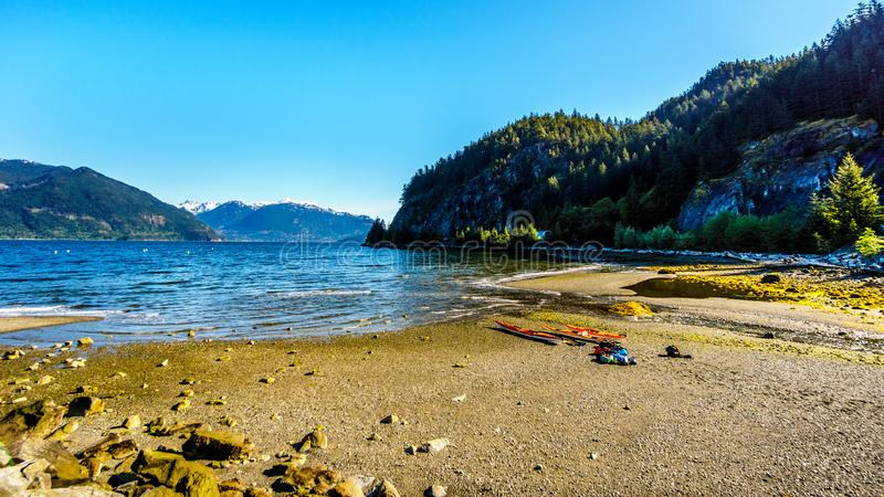 Kayakers ready to explore the waters of Howe Sound. And surrounding mountains. Viewed from the Porteau Cove ferry docks stock photography