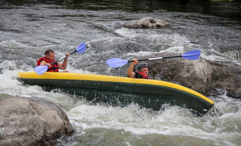 Kayakers slåss det vita vattnet i en Pivdenny felflod De och deras kajak bläddrar över royaltyfri foto
