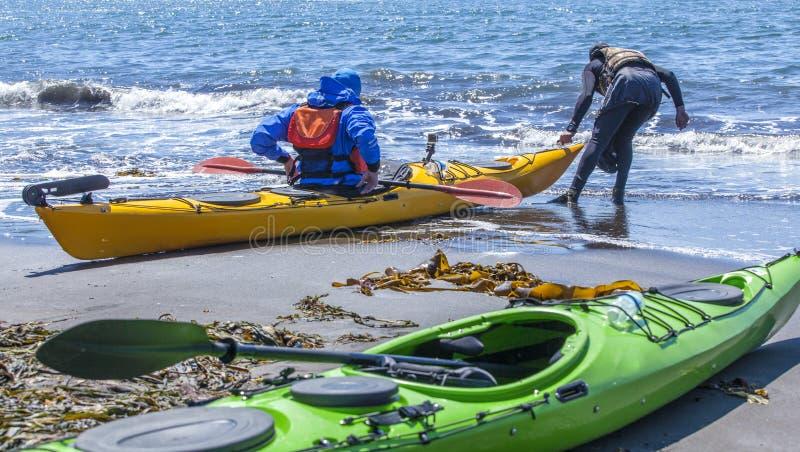 Kayakers sulla costa della sabbia dell'oceano Pacifico immagine stock libera da diritti