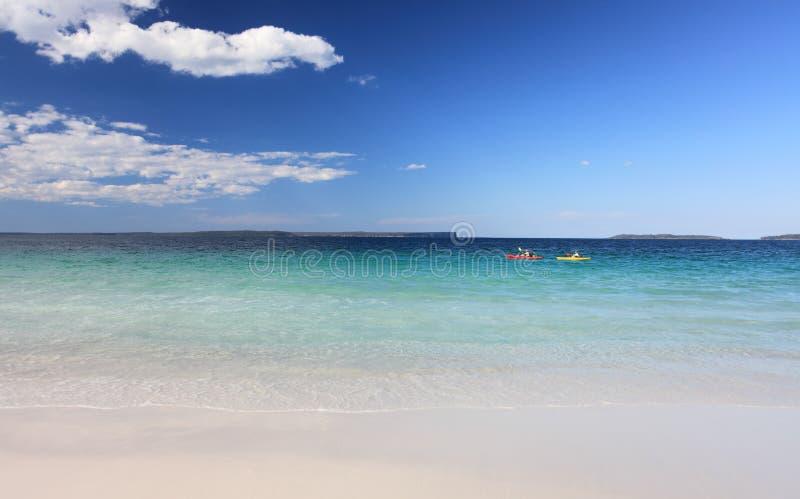 Kayakers tycker om den australiska stranden för kristallklart vatten arkivbilder