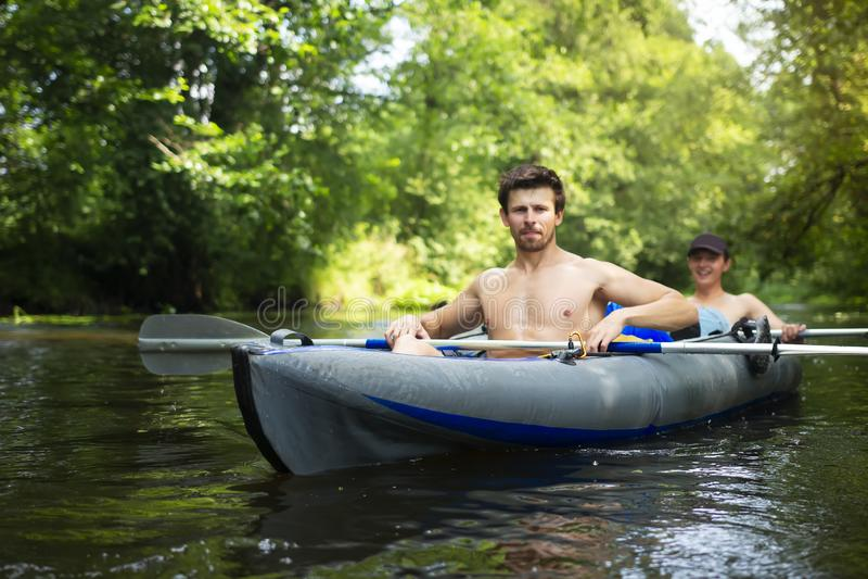 Kayaking ao longo do rio selvagem Dois homens no barco Homem novo com os remos na canoa Lazer no caiaque Turismo ativo na naturez fotografia de stock royalty free