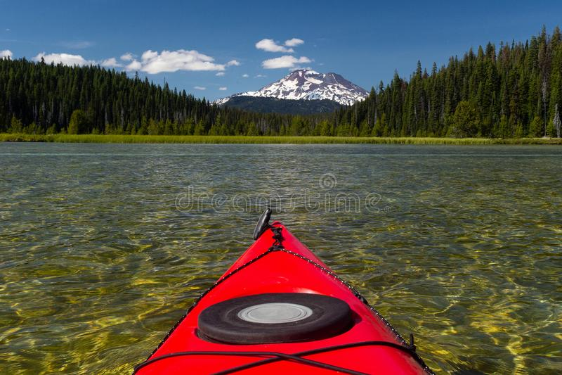 Kayaking beautiful lake in summer toward mountain peak stock photos