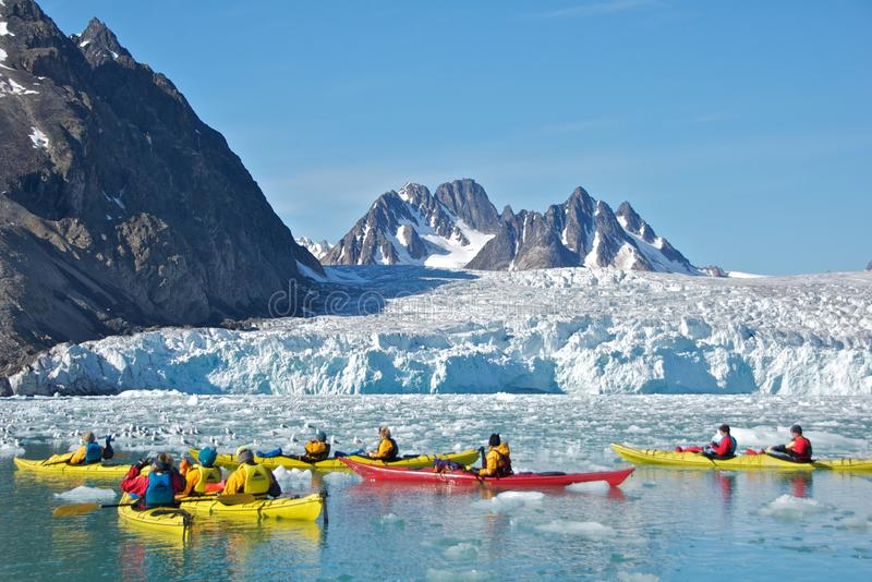 Kayaking Close to Monaco Glacier in Svalbard. In July, the travelers were able to do kayaking near Monaco Glacier on the calm water in Svalbard stock photos