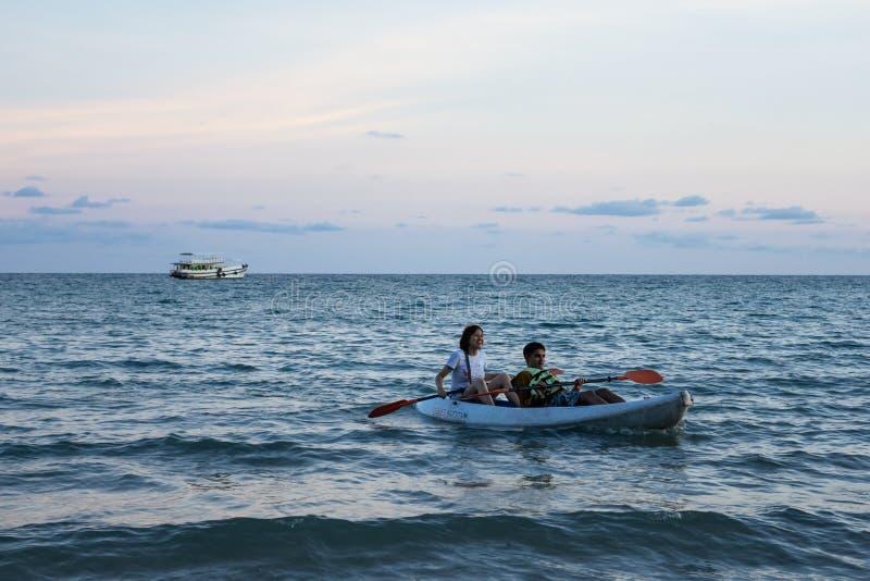 Kayaking de touristes de couples au-dessus de la surface de vague de mer qui s'est reflétée avec la couleur bleue et pourpre de photos libres de droits