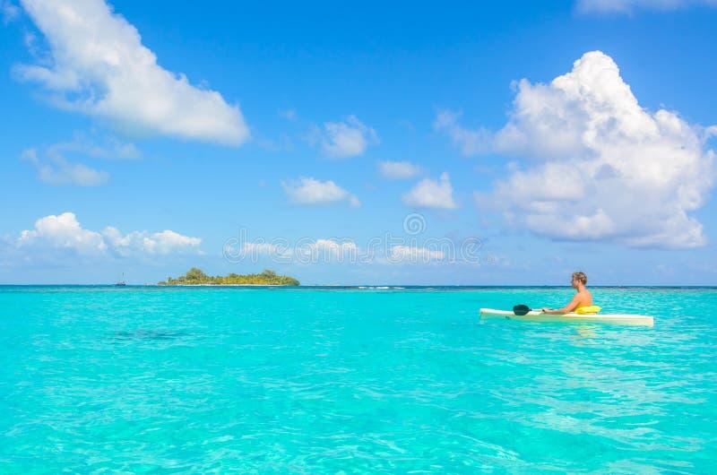 Kayaking en el paraíso tropical - canoa que flota en el agua transparente de la turquesa, mar del Caribe, Belice, islas de Cayes fotos de archivo