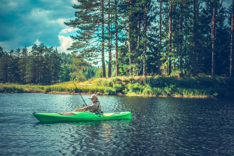 Fly Fishing From Kayak. Kayaking and Fly Fishing. Caucasian Fisherman with a Rod in the Kayak. Summer Recreation Theme royalty free stock photo