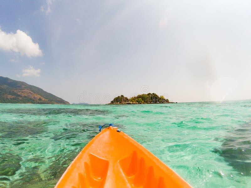 kayaking i kristallklart tropiskt vatten - kajaköverskrift till den isolerade stranden i den Ko Tarutao nationalparken royaltyfri fotografi