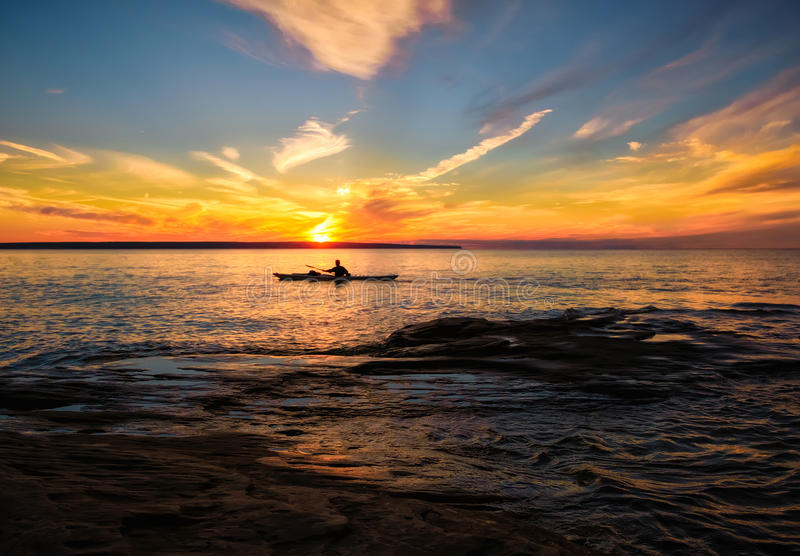 Kayaking Lake Superior in Summer, Michigan. A man kayaks in Lake Superior, in the Pictured Rocks National Lakeshore, Upper Peninsula of Michigan, as the sun is stock images